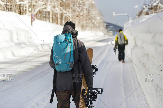Snowboarders Walking Along Snow Covered Side Walk To Resort In Niseko, Japan