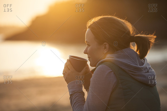 A Woman Enjoys A Hot Drink At A Beach Near Tofino, British Columbia, Canada