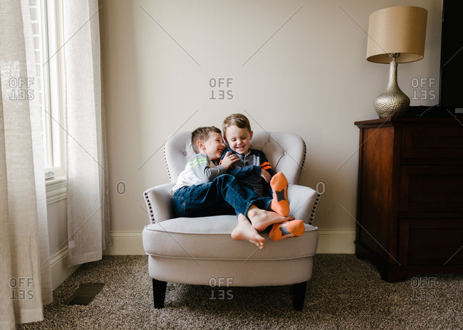Two boys giggling in chair
