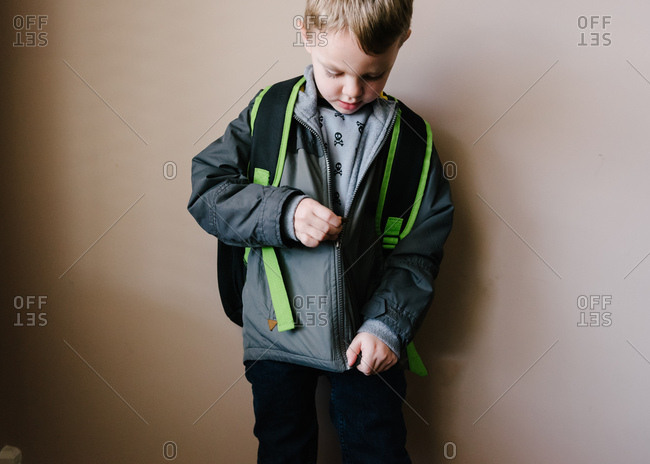 boy with backpack zipping his jacket stock photo offset. Black Bedroom Furniture Sets. Home Design Ideas