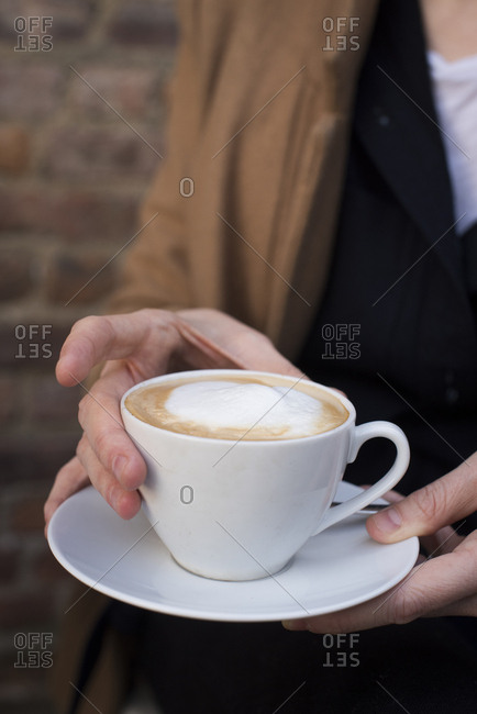 Woman holding a mug of cappuccino