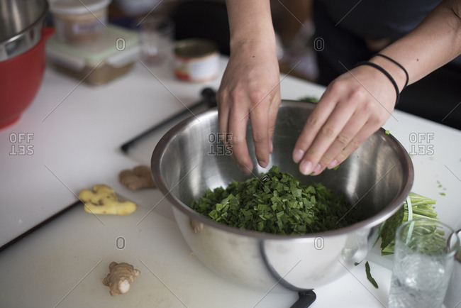 Person putting chopped green onion in bowl