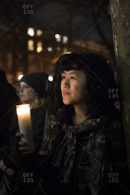 Washington Square Park, New York City - January 25, 2017: Woman with candle at political rally