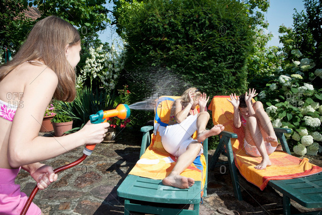 Girl sprays water on mum and sister