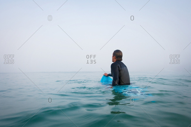 Man sitting on surfboard in the water