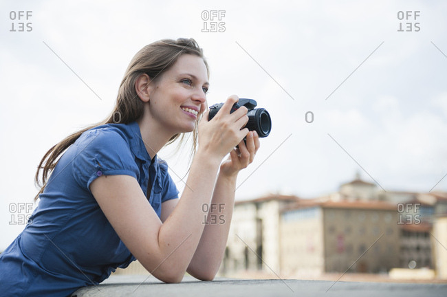 Woman leaning against wall, holding camera