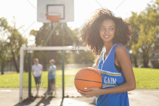 Smiling young female basketball player holding basketball