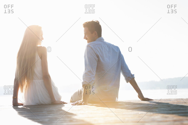 Young couple sitting on jetty, looking at each other, rear view