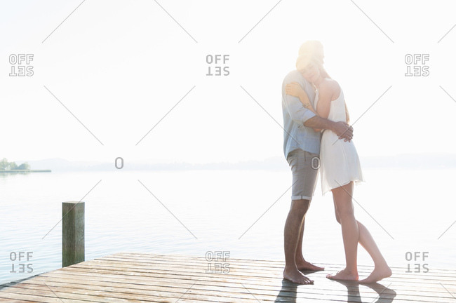 Young couple standing on jetty at sunset, embracing