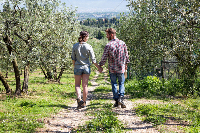 Full length rear view of couple hand in hand walking on dirt track