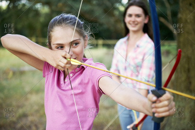 Girl practicing archery aiming with bow and arrow
