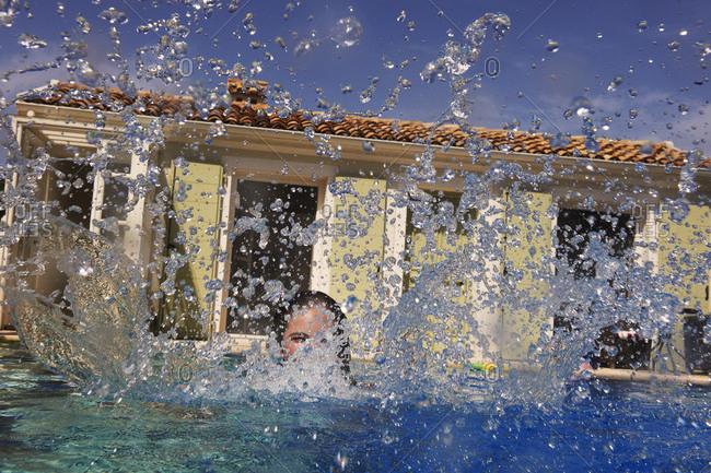 Teenage girl splashing in outdoor swimming pool