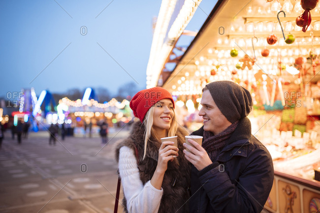 Young couple drinking mulled wine at Xmas festival, Hyde Park, London, UK