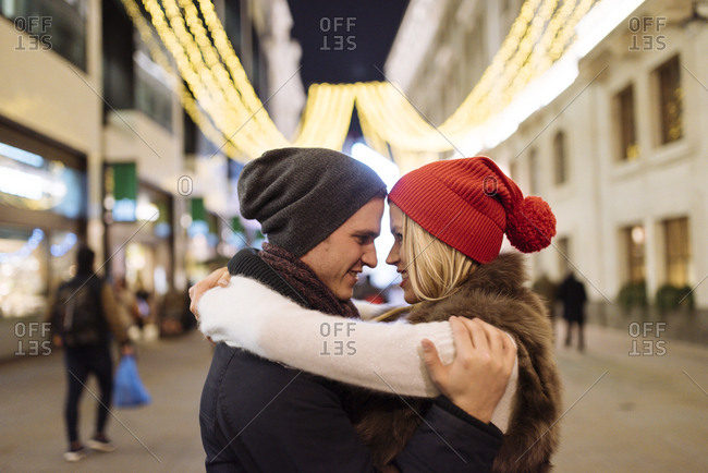 Romantic young couple hugging on street at xmas, London, UK