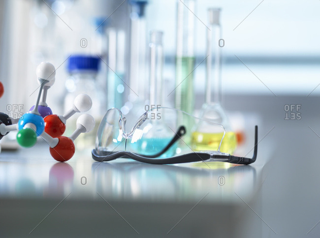 Safety glasses and molecular model on laboratory bench, scientific equipment in background