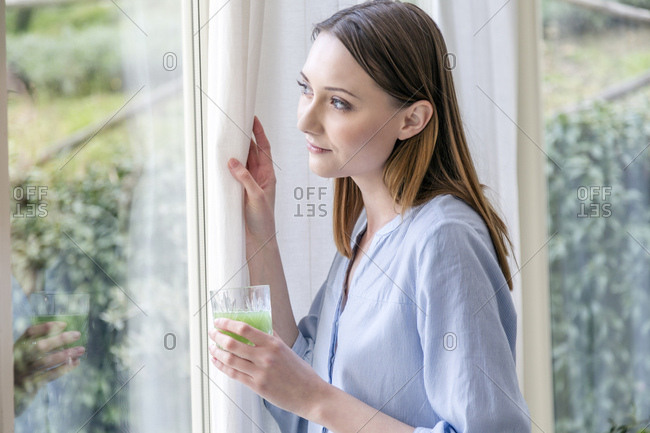 Woman looking out of window holding green smoothie