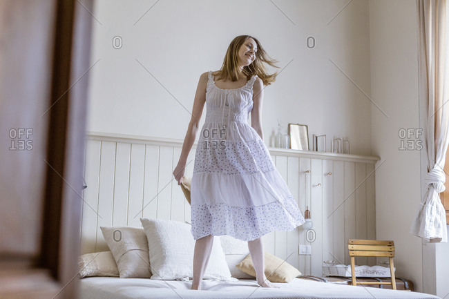 Woman wearing white dress jumping on bed