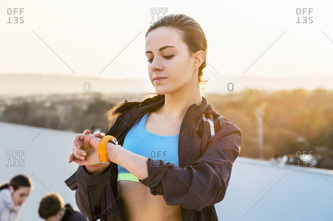Young woman, outdoors, looking at activity tracker