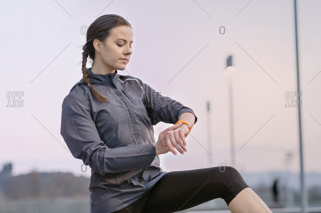 Young woman, wearing sports clothing, looking at activity tracker