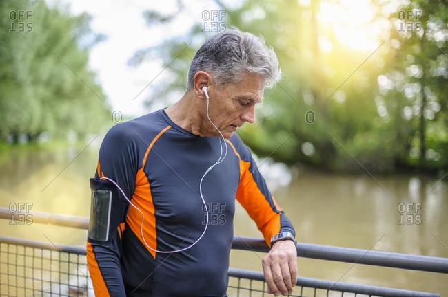 Senior male runner looking at smart watch on footbridge