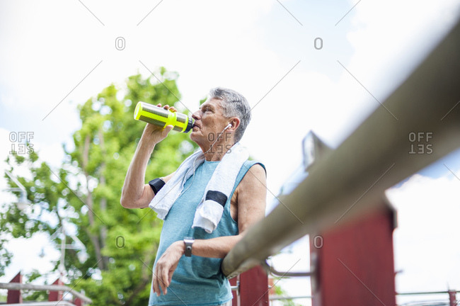 Senior male runner drinking from water bottle on footbridge