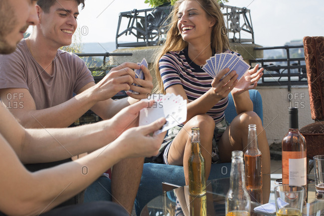 Adult friends playing card games at roof terrace party