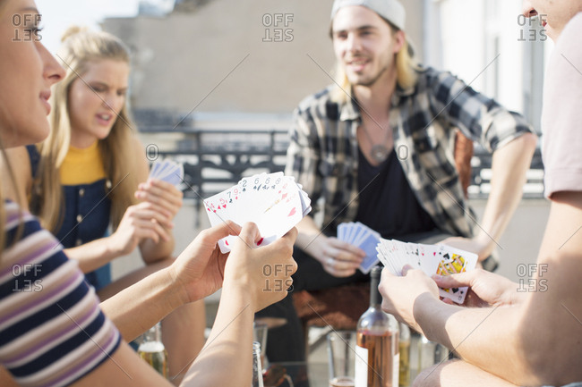 Young adults playing card game at roof terrace party, Budapest, Hungary