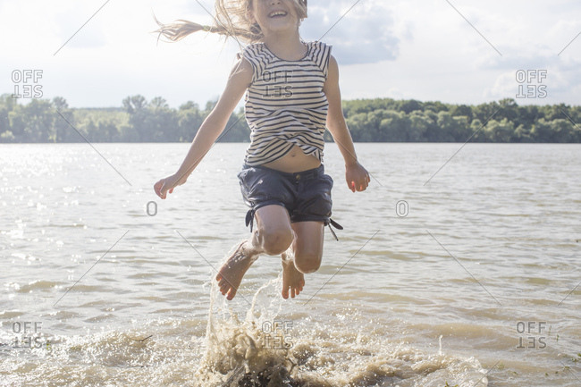Girl jumping and splashing in river