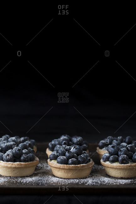 Blueberry tarts on a black background