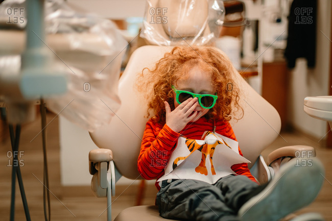 Child sitting in chair waiting for dentist