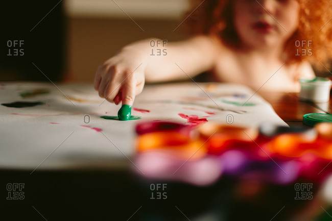Young boy finger painting - Offset