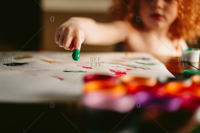 Child finger painting with green paint