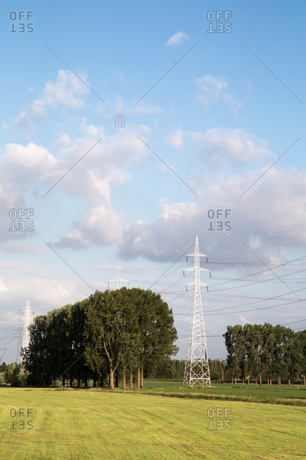 Power lines in a beautiful green field