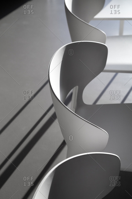Light playing along the curves of white chairs