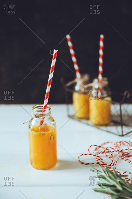 Juice in glass bottles with straws