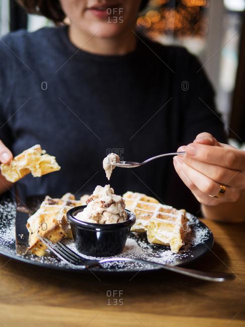 Woman eating a waffle dish