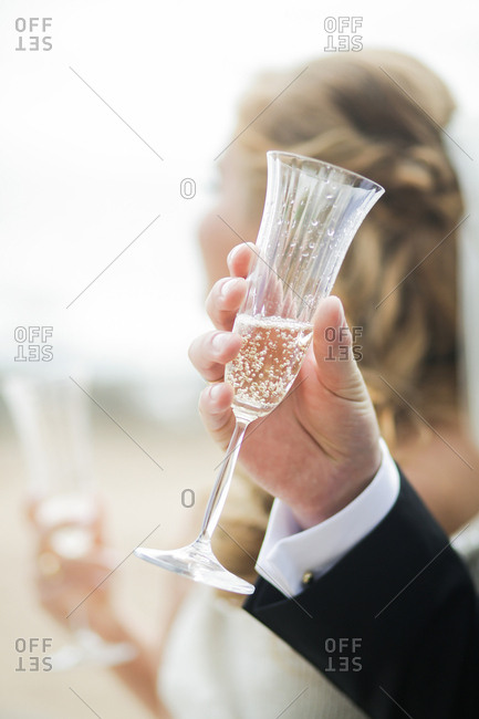 Groom holding champagne glass