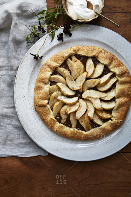Pear and chocolate galette dessert with a side of whipped cream