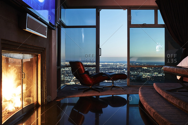 Los Angeles, California - February 24, 2017: Interior of room with fireplace and windows overlooking city lights of Los Angeles at dusk in Hollywood Hills home