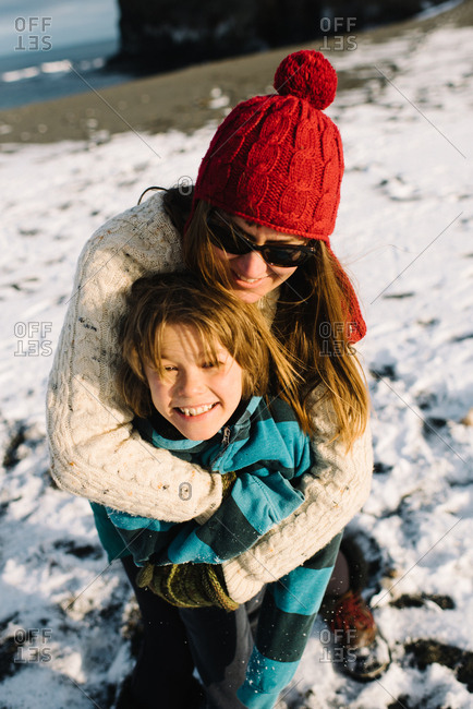 Mother hugging her son outside in the snow
