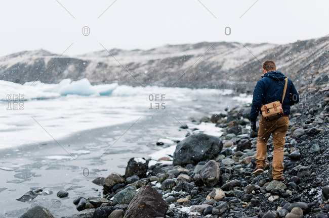 Young man trudging through the snow beside Jokulsarlon Glacier Lake in southern Iceland