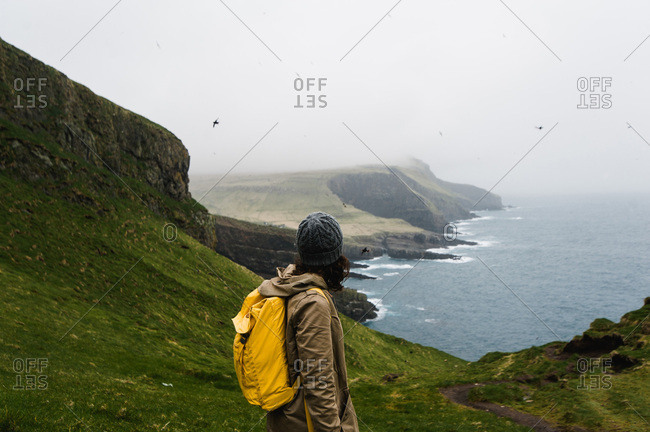 Woman gazing at puffins circling over sea and mountains, Mykines, Faroe Islands