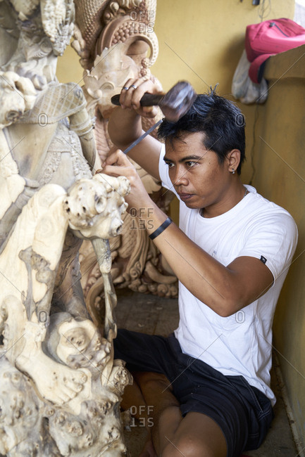 Bali, Indonesia - February 19, 2017: Balinese man hand-crafting wood relief carvings and wood sculptures