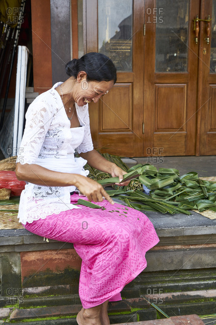 Ubud, Bali, Indonesia - February 19, 2017: Balinese woman making worship baskets at palace in Ubud