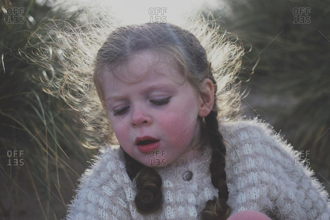 Close up a little girl outdoors with frizzy pigtails