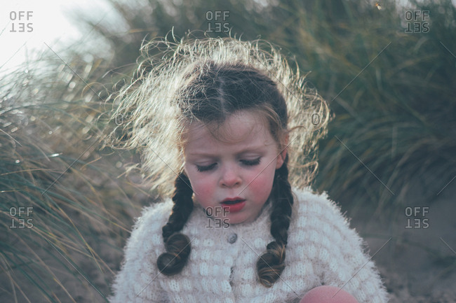 Portrait of a little girl outdoors with frizzy hair and rosy cheeks