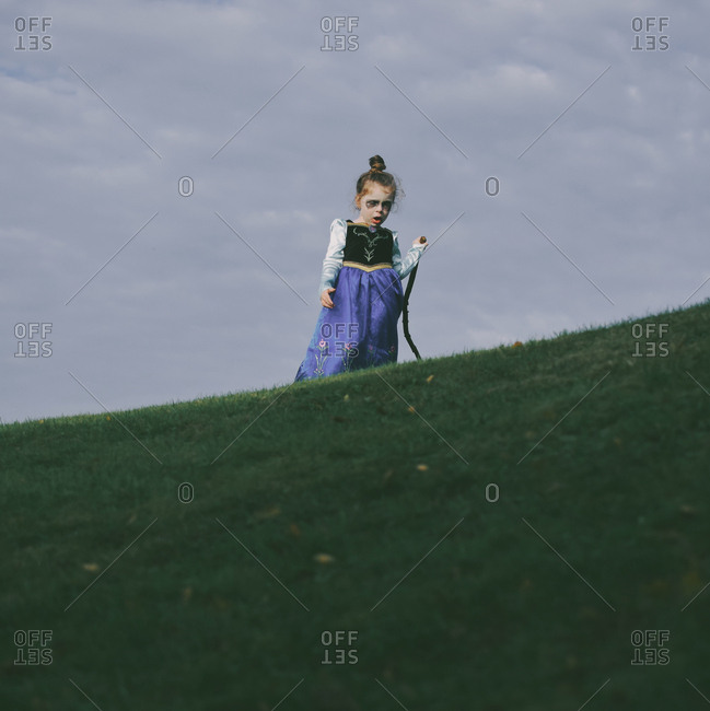 Girl walking on a hill wearing a zombie princess costume