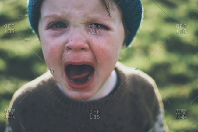 Boy outdoors crying and screaming
