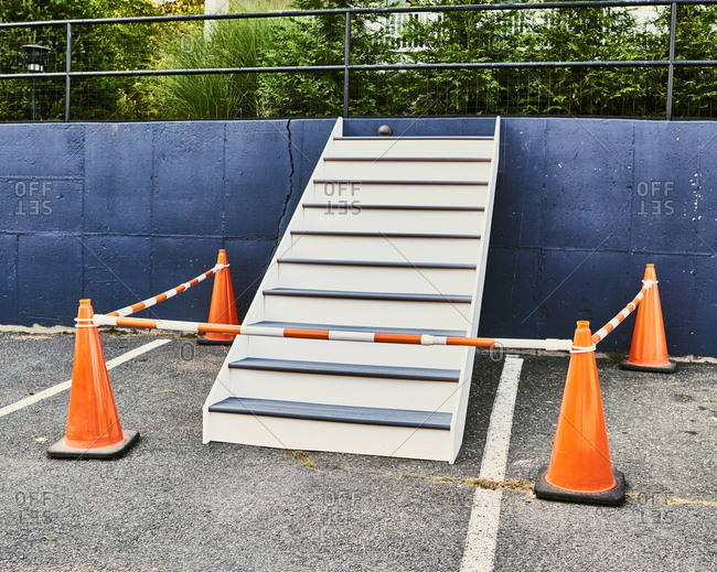 Stairs against blue wall in parking lot sectioned off with traffic cones
