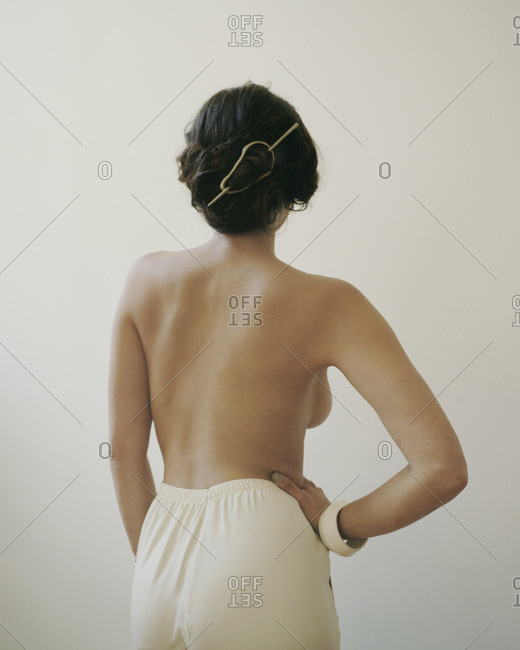Bare back of woman standing with hand on hip